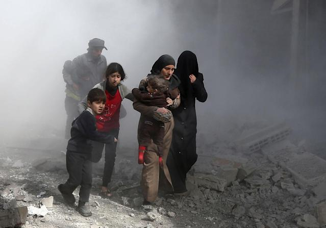 <p>Syrian civilians flee from reported regime air strikes in the rebel-held town of Jisreen, in the besieged Eastern Ghouta region on the outskirts of the capital Damascus, on Feb. 8, 2018. (Photo: Abdulmonam Eassa/AFP/Getty Images) </p>
