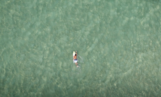 A surfer swims at Barra da Tijuca beach in Rio de Janeiro February 22, 2013. REUTERS/Ricardo Moraes (BRAZIL - Tags: TRAVEL SOCIETY SPORT TPX IMAGES OF THE DAY) - RTR3E4RH
