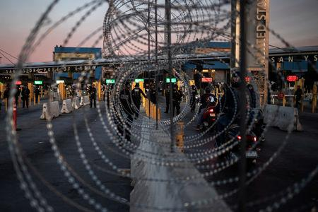 U.S. Customs and Border Protection (CBP) Special Response Team (SRT) officers are seen through concertina wire after the San Ysidro Port of Entry land border crossing was temporarily closed to traffic in Tijuana, Mexico November 19, 2018. REUTERS/Adrees Latif