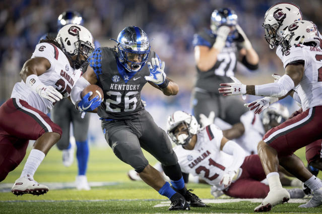 Kentucky running back Benny Snell Jr. (26) carries the ball between several South Carolina defenders during the first half of an NCAA college football game in Lexington, Ky., Saturday, Sept. 29, 2018. (AP Photo/Bryan Woolston)