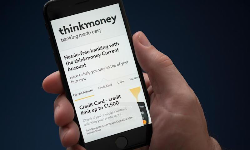 A man looks at his iPhone, which displays the Thinkmoney logo