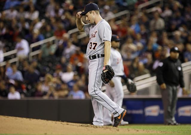 Detroit Tigers pitcher Max Scherzer adjusts his cap after giving up a walk to Minnesota Twins' Brian Dozier during the first inning of a baseball game, Wednesday, Sept. 25, 2013, in Minneapolis. (AP Photo/Jim Mone)