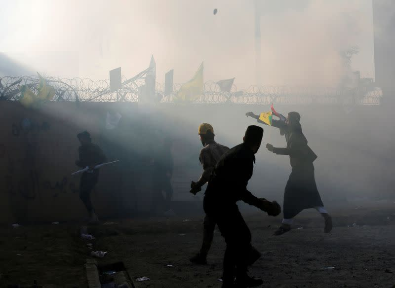 FILE PHOTO: Protesters and militia fighters throw stones towards the U.S. Embassy during a protest to condemn air strikes on bases belonging to Hashd al-Shaabi (paramilitary forces), in Baghdad
