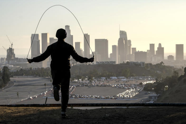 FILE - In this Jan. 4, 2021, file photo, Alex Gonzalez, 19, jumps rope on Angel's Point at Elysian Park as motorists wait in long lines to take a coronavirus test in a parking lot at Dodger Stadium, in Los Angeles. Coronavirus deaths and cases per day in the U.S. dropped markedly over the past couple of weeks but are still running at alarmingly high levels, and the effort to snuff out COVID-19 is becoming an ever more urgent race between the vaccine and the mutating virus. (AP Photo/Ringo H.W. Chiu)