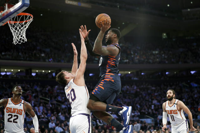 New York Knicks forward Julius Randle (30) leaps for a shot over Phoenix Suns forward Dario Saric (20) as Suns center Deandre Ayton (22) and Suns guard Ricky Rubio (11) watch from the floor during the first half of an NBA basketball game in New York, Thursday, Jan. 16, 2020. (AP Photo/Kathy Willens)