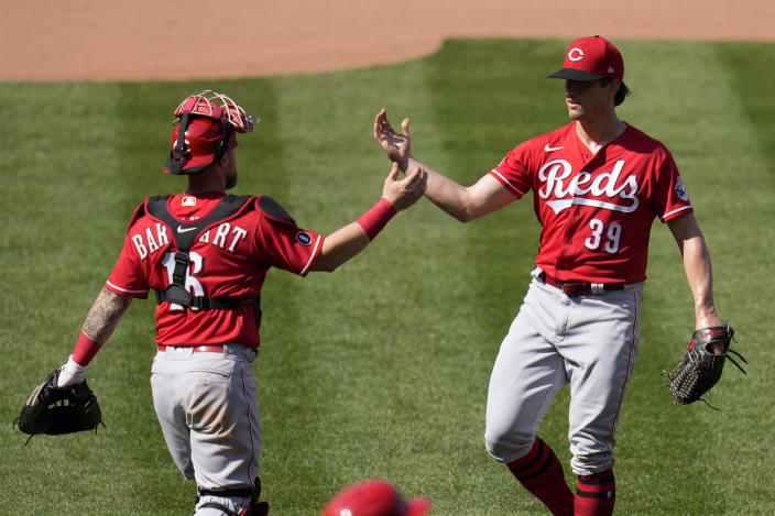 Cincinnati Reds pitcher Lucas Sims (39) and catcher Tucker Barnhart celebrate a 5-2 victory over the St. Louis Cardinals in a baseball game Saturday, June 5, 2021, in St. Louis. (AP Photo/Jeff Roberson)