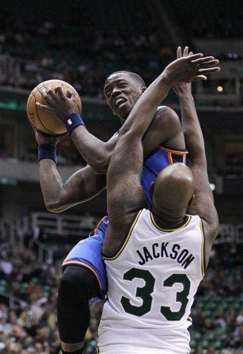 Oklahoma City Thunder guard Reggie Jackson, top, drives to the basket as Utah Jazz forward Darnell Jackson (33) defends in the second quarter during an preseason NBA basketball game on Friday, Oct. 12, 2012, in Salt Lake City. (AP Photo/Rick Bowmer)