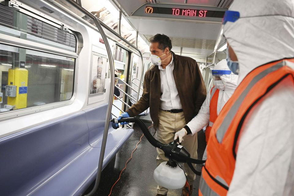 In this photo provided by the Office of Governor Andrew M. Cuomo, New York Gov. Cuomo tries out a spraying device which is part of a three-step disinfecting process of a New York City subway car at the Corona Maintenance Facility in the Queens borough of of New York, Saturday, May 2, 2020. Cuomo announced on Thursday April 30, that New York City is shutting down its subway system each day from 1 a.m. to 5 a.m. to increase cleaning of trains and stations during the coronavirus crisis. (Kevin P. Coughlin/Office of Governor Andrew M. Cuomo via AP)
