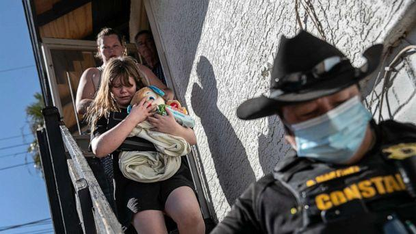 PHOTO: Maricopa County constable Darlene Martinez escorts a family out of their apartment after serving an eviction order for non-payment on Sept. 30, 2020. in Phoenix. (John Moore/Getty Images)