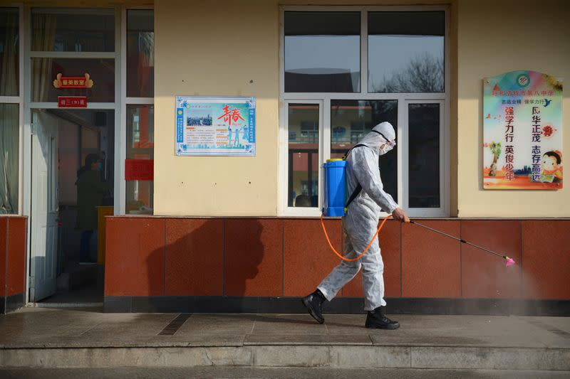 Worker in a protective suit sprays disinfectant at a middle school in Hohhot