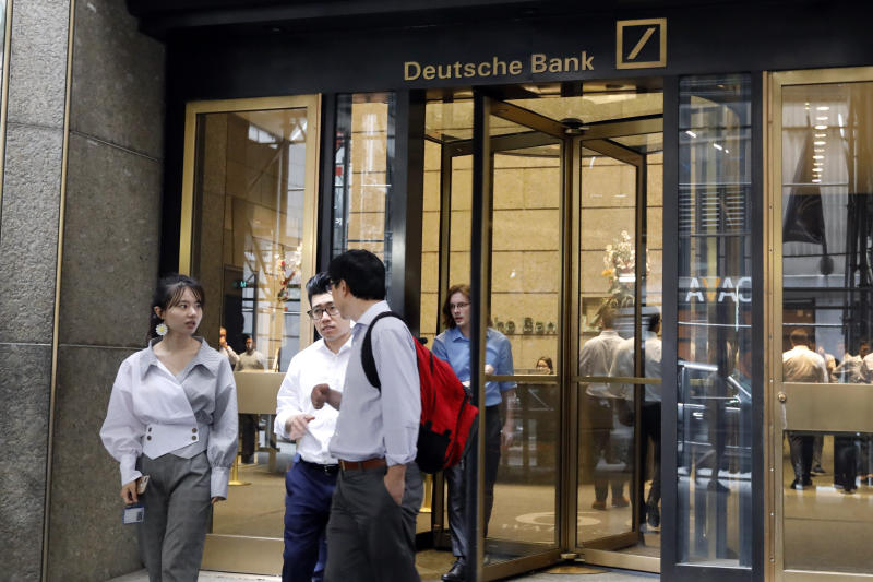 People leave Deutsche Bank in New York, Monday, July 8, 2019. Germany's struggling Deutsche Bank said Sunday it would cut 18,000 jobs by 2022, downsizing its volatile investment banking division in a restructuring aimed at restoring consistent profitability and better returns to shareholders. (AP Photo/Richard Drew)