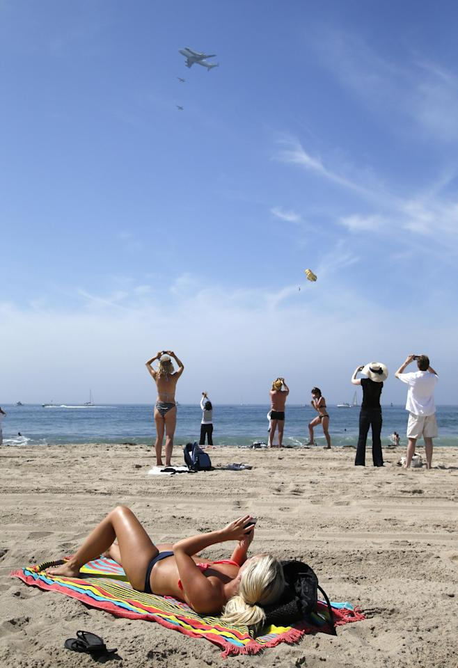 Spectators take pictures as the Space Shuttle Endeavour mounted on NASA's Shuttle Carrier Aircraft (SCA) flies near Santa Monica, Calif., Friday, Sept. 21, 2012. (AP Photo/Jae C. Hong)