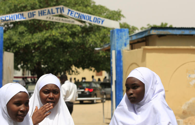 FILE In this Thursday, June 6, 2013 file photo, young women stand in front of a school in Maiduguri, Nigeria. Boko Haram, the radical group that once attacked only government institutions and security forces, is increasingly targeting civilians. Some 155,000 square kilometers (60,000 square miles) of Nigeria are now under a state of emergency. On Friday, June 21, 2013, villagers streamed into Maiduguri from the Gwoza hills, saying Boko Haram fighters were threatening a bloodbath in the area where they appear to have regrouped, scrubby mountains with rock caves some 150 kilometers (90 miles) from the city. (AP Photo/Jon Gambrell, File)
