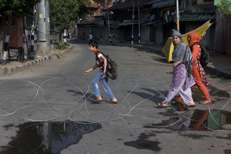 Kashmiri children accompanied by their mother walk past barbwire setup as road blockade by Indian paramilitary soldiers during lockdown in Srinagar, Indian controlled Kashmir, Friday, Aug. 23, 2019. The latest crackdown began just before Prime Minister Narendra Modi's Hindu nationalist-led government stripped Jammu and Kashmir of its semi-autonomy and its statehood, creating two federal territories. (AP Photo/Dar Yasin)
