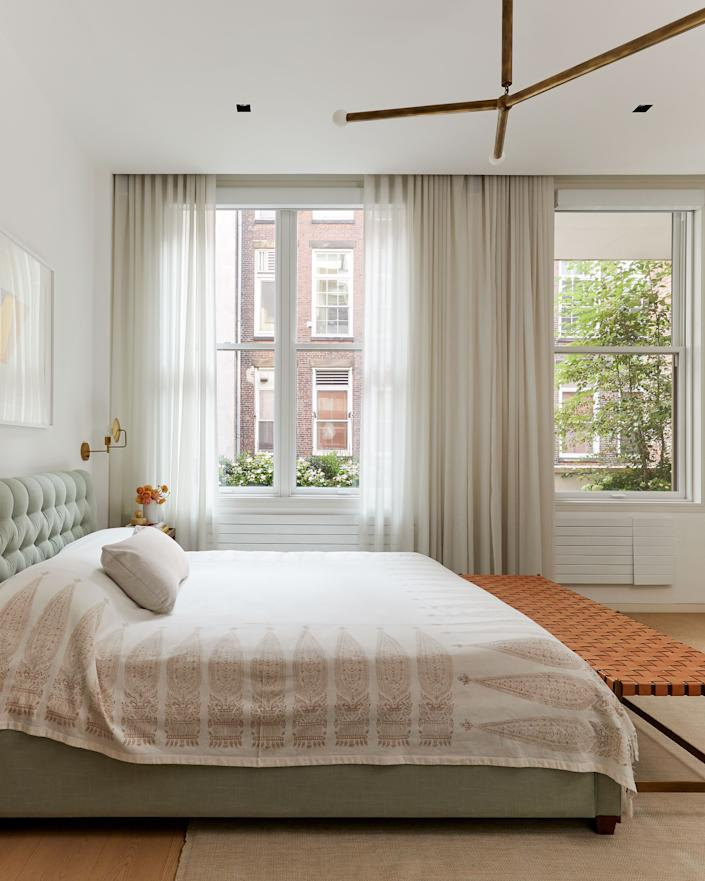 """<div class=""""caption""""> Custom window dressings help soften the loft's sharp linearity in the master suite, where the bed is topped with linens by <a href=""""https://lesindiennes.com/"""" rel=""""nofollow noopener"""" target=""""_blank"""" data-ylk=""""slk:Les Indiennes"""" class=""""link rapid-noclick-resp"""">Les Indiennes</a> and flanked by <a href=""""https://lawsonfenning.com/"""" rel=""""nofollow noopener"""" target=""""_blank"""" data-ylk=""""slk:Lawson Fenning"""" class=""""link rapid-noclick-resp"""">Lawson Fenning</a> nightstands. The bench is by <a href=""""https://www.thomashayesstudio.com/"""" rel=""""nofollow noopener"""" target=""""_blank"""" data-ylk=""""slk:Thomas Hayes Studio"""" class=""""link rapid-noclick-resp"""">Thomas Hayes Studio</a>, the sconces are by <a href=""""https://www.workstead.com/"""" rel=""""nofollow noopener"""" target=""""_blank"""" data-ylk=""""slk:Workstead"""" class=""""link rapid-noclick-resp"""">Workstead</a>, and the pendant light is by <a href=""""https://apparatusstudio.com/"""" rel=""""nofollow noopener"""" target=""""_blank"""" data-ylk=""""slk:Apparatus"""" class=""""link rapid-noclick-resp"""">Apparatus</a>. </div>"""