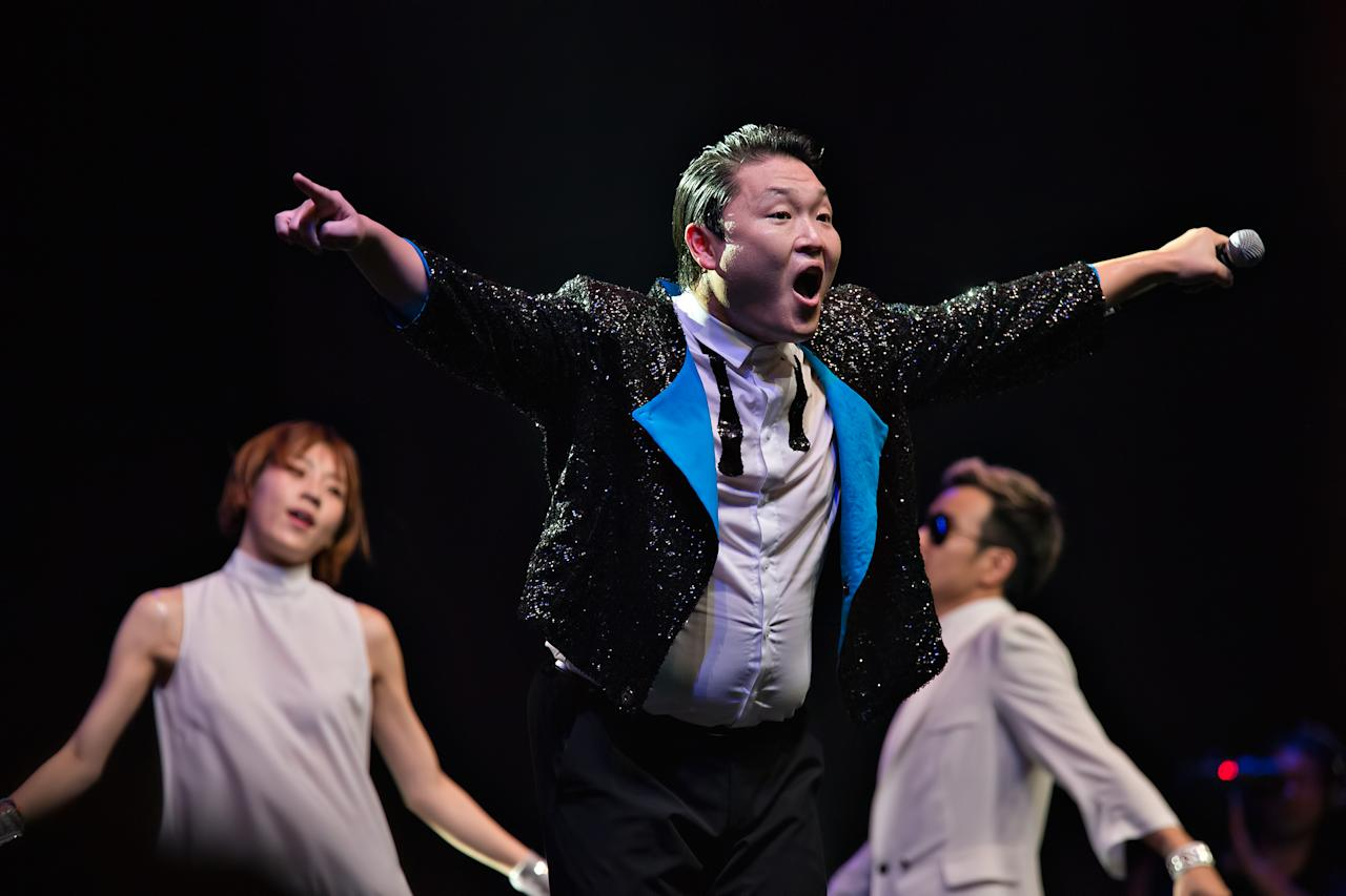 "Dressed in his trademark black suit and sunglasses, Psy launched into his three-song setlist with rap number ""Champion"", to which he got the fanatical audience to chant ""Champion, Champion"" with him."
