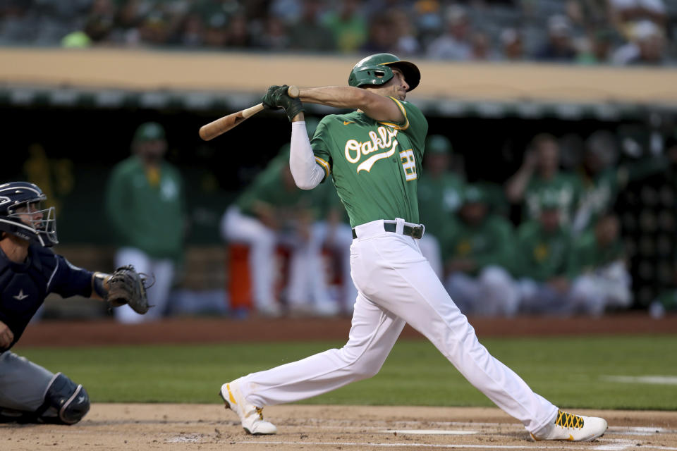 Oakland Athletics' Matt Olson, right, hits a solo home run in front of Seattle Mariners' Tom Murphy, left, during the first inning of a baseball game in Oakland, Calif., Tuesday, Sept. 21, 2021. (AP Photo/Jed Jacobsohn)