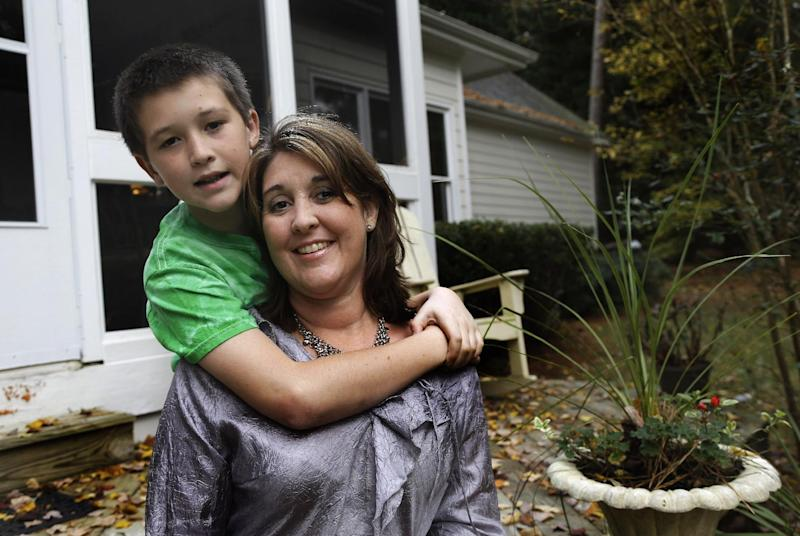 In this Tuesday, Nov. 5, 2013 photo, Jill Morin, right, poses for photos with her son Kyle at their home in Raleigh, N.C. Morin suffers from a serious heart condition and suffered a cardiac arrest in 2009. Morin and hundreds of thousands of other people with preexisting chronic conditions who are covered through high risk insurance pools will see their coverage dissolve by year's end. (AP Photo/Gerry Broome)
