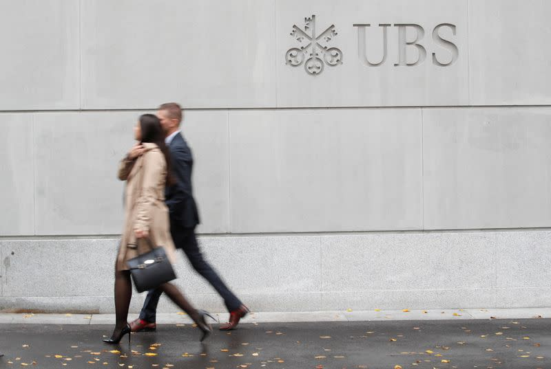 People walk past a logo of Swiss bank UBS in Zurich,