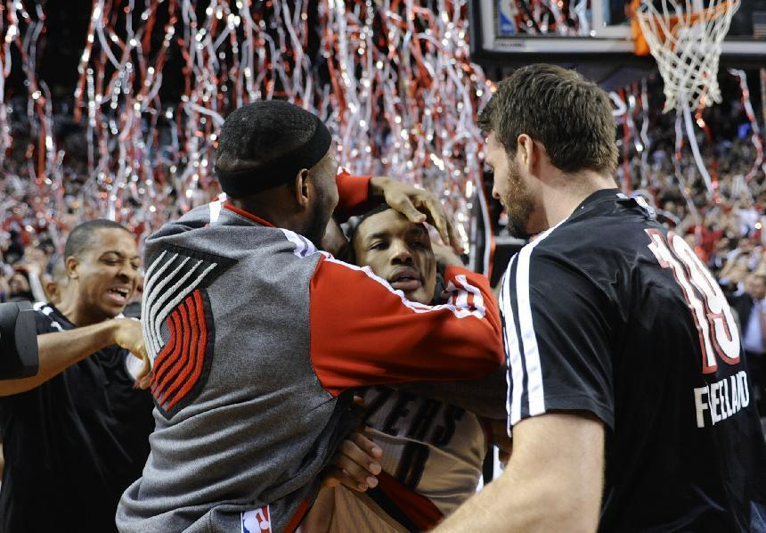 Portland Trail Blazers' Damian Lillard, center, celebrates his winning shot against the Houston Rockets during the last .9 of a second of game six of an NBA basketball first-round playoff series game in Portland, Ore., Friday May 2, 2014. The Trail Blazers won the series in a 99-98 win. (AP Photo/Greg Wahl-Stephens)
