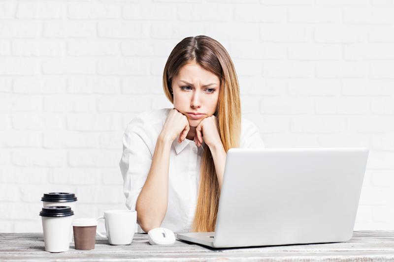 Woman staring at laptop with sad expression
