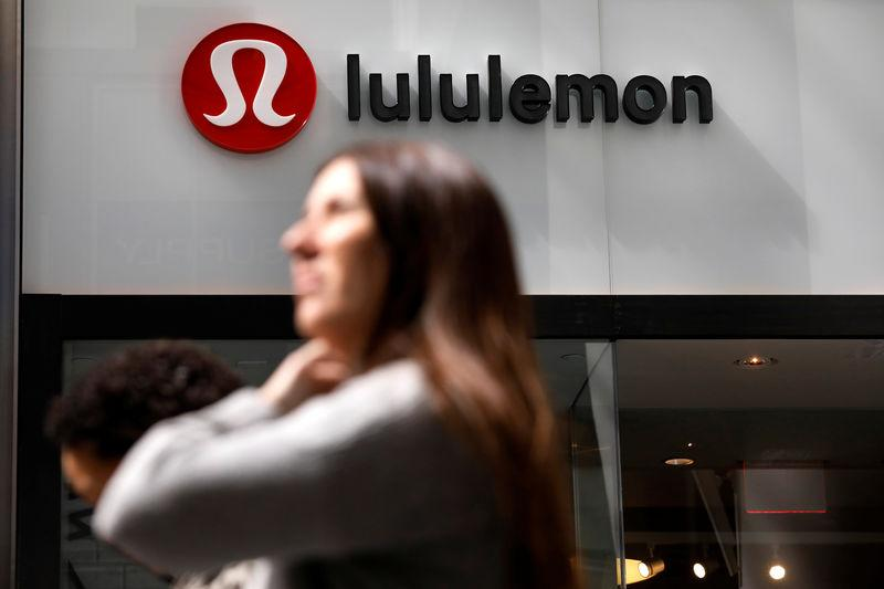 People walk past a store by yogawear retailer Lululemon Athletica in New York