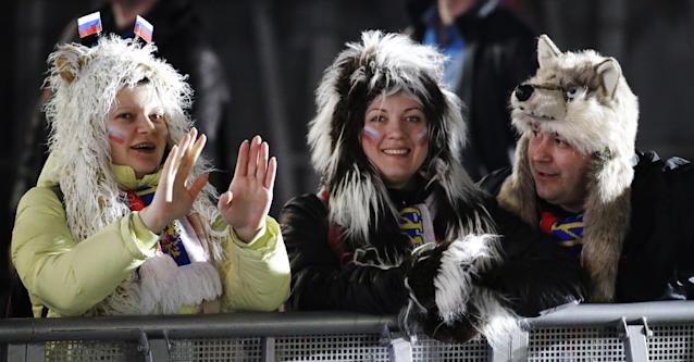 Fans chat before the medals ceremonies begin at the 2014 Winter Olympics, Monday, Feb. 10, 2014, in Sochi, Russia. (AP Photo/Morry Gash)