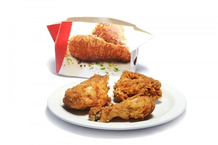 Kentucky Fried Chicken Box with chicken pieces in the foreground, KFC, fast food, Yum! Brands, Inc.(NYSE:YUM) shutterstock_310315346