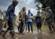 """Men gather to speak to a militia fighter Kibret Bidere, with an injured arm, center, near the village of Chenna Teklehaymanot, in the Amhara region of northern Ethiopia Thursday, Sept. 9, 2021. At the scene of one of the deadliest battles of Ethiopia's 10-month Tigray conflict, witness accounts reflected the blurring line between combatant and civilian after the federal government urged all capable citizens to stop Tigray forces """"once and for all."""" (AP Photo)"""