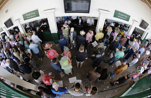 FILE - In this May 3, 2014, file photo, taken with a fisheye lens, fans line up to place bets before the 140th running of the Kentucky Derby horse race at Churchill Downs in Louisville, Ky. Next months Kentucky Derby will run without fans at Churchill Downs. The historic track cited rises in COVID-19 cases in the Louisville area. (AP Photo/Charlie Riedel, File)