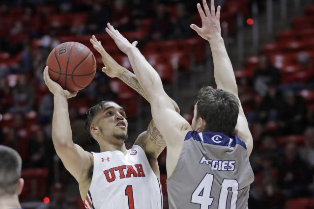 Utah forward Timmy Allen (1) shoots as UC Davis guard Elijah Pepper (40) defends during the second half of an NCAA college basketball game Friday, Nov. 29, 2019, in Salt Lake City. (AP Photo/Rick Bowmer)