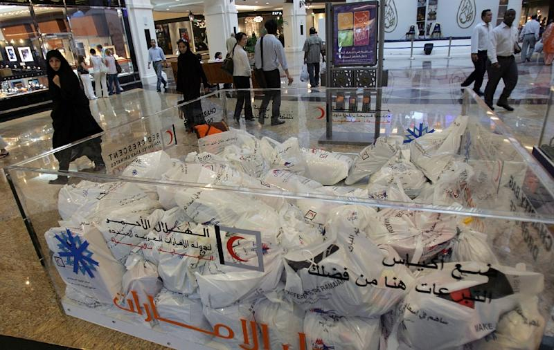 Emiratis and foreigners pass next to donation boxes at a shopping centre in Dubai, October 11, 2007 (AFP Photo/Karim Sahib)