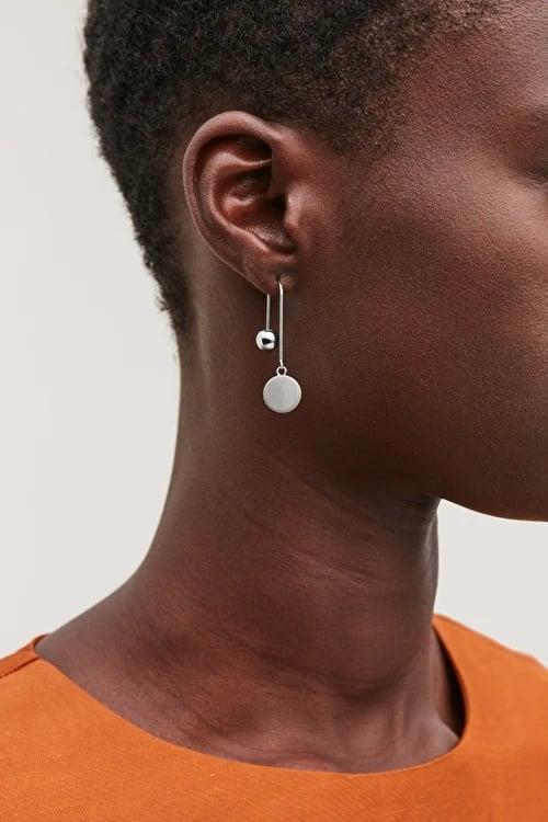 """<p><a href=""""https://www.popsugar.com/buy/COS-Ball-Disc-Drop-Earrings-497276?p_name=COS%20Ball%20and%20Disc%20Drop%20Earrings&retailer=cosstores.com&pid=497276&price=35&evar1=fab%3Aus&evar9=46708649&evar98=https%3A%2F%2Fwww.popsugar.com%2Ffashion%2Fphoto-gallery%2F46708649%2Fimage%2F46709070%2FCOS-Ball-Disc-Drop-Earrings&list1=shopping%2Cjewelry%2Cunder%20%2450%2Caffordable%20shopping%2Cjewelry%20shopping&prop13=mobile&pdata=1"""" rel=""""nofollow noopener"""" class=""""link rapid-noclick-resp"""" target=""""_blank"""" data-ylk=""""slk:COS Ball and Disc Drop Earrings"""">COS Ball and Disc Drop Earrings</a> ($35)</p>"""