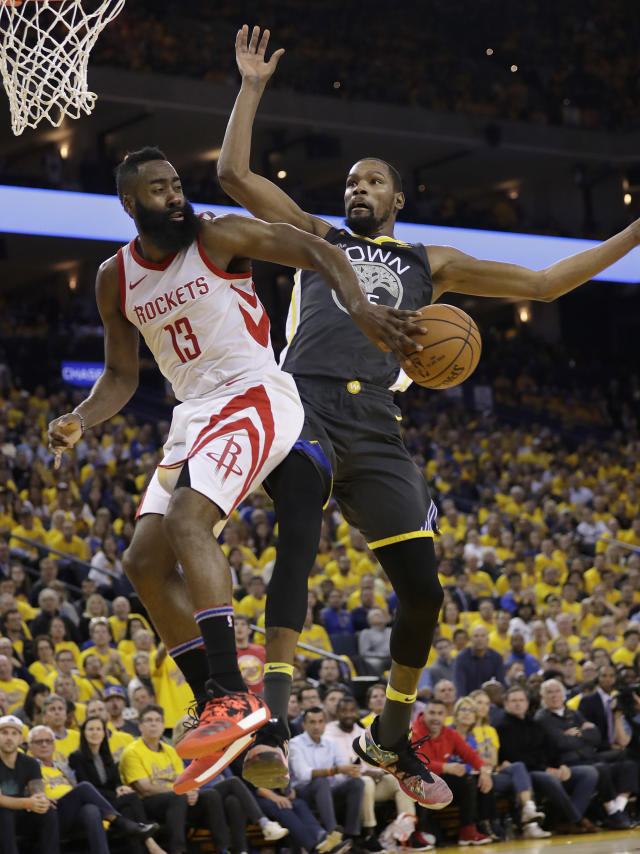 Houston Rockets guard James Harden (13) passes behind Golden State Warriors forward Kevin Durant during the first half of Game 4 of the NBA basketball Western Conference Finals in Oakland, Calif., Tuesday, May 22, 2018. (AP Photo/Marcio Jose Sanchez)