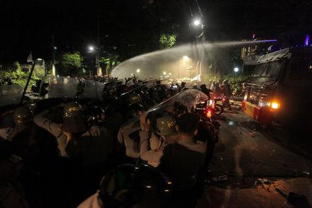 Police use a water cannon to disperse a crowd gathered outside the Indonesian Legal Aid Foundation during an anti-communist protest in Jakarta