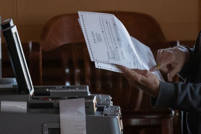 Election official points towards mail in ballot while scanning votes for the U.S. presidential election in Marfa, Texas