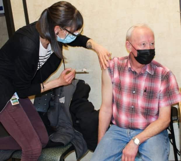 Gary Harris receives a COVID-19 vaccine in Grande Prairie, Alta., on March 11, 2021. The northwestern Alberta city lags behind the rest of the province in vaccine uptake.  (AHS - image credit)