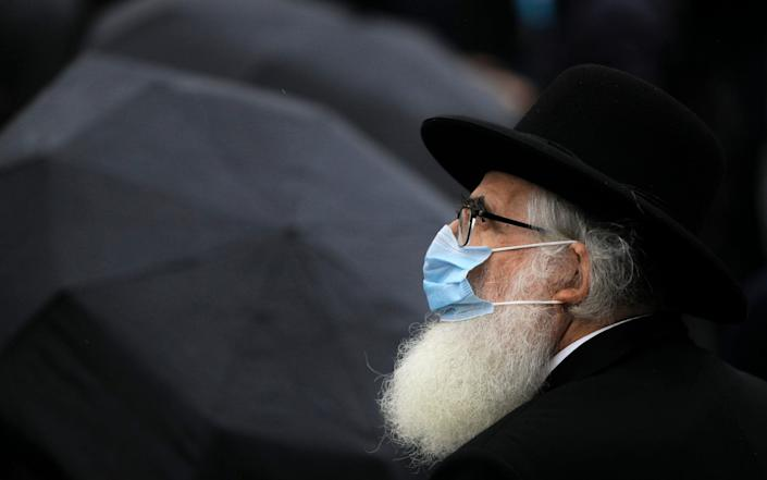 Rabbi Rafael Schaffer, wearing a face mask, stands outside the Holocaust memorial during the National Holocaust Remembrance Day commemorations in Bucharest, Romania - AP