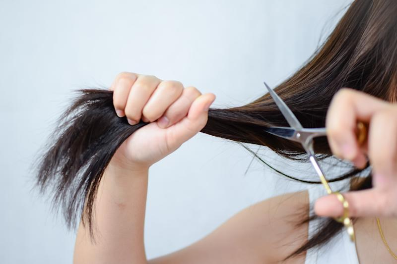 Midsection Of Woman Cutting Hair Against White Background