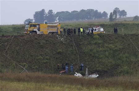 Investigators and firefighters stand in front of a wreckage of a twin propeller airplane at South Africa's Lanseria airport outside Johannesburg