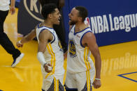 Golden State Warriors guard Stephen Curry, right, celebrates with guard Jordan Poole during the second half of an NBA basketball game against the Memphis Grizzlies in San Francisco, Sunday, May 16, 2021. (AP Photo/Jeff Chiu)