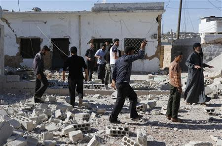 People inspect a site hit by what activists said were barrel bombs dropped by forces loyal to Syria's President Assad in al-Letmana village in Hama province