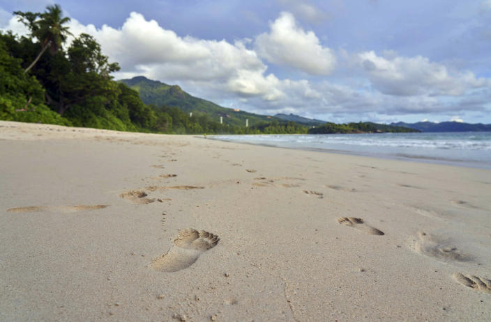 FILE - In this Friday, March 1, 2019 file photo, footprints are seen in the sand on a beach on Mahe island, Seychelles. The president of the Indian Ocean island nation of Seychelles says he hopes enough residents will soon be vaccinated against COVID-19 to stop the spread of the virus, hoping to achieve herd immunity by mid-March 2021 by vaccinating about 70% of the population. (AP Photo/David Keyton, File)