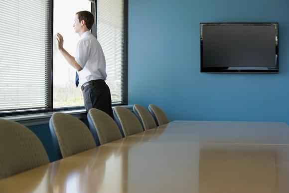 Man in empty conference room standing and looking out the window.