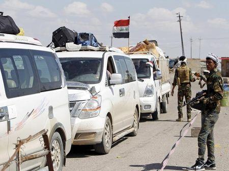Families who have returned to their homes drive past a checkpoint guarded by Sunni fighters who have joined Shiite militia groups known collectively as Hashid Shaabi (Popular Mobilization), who are allied with Iraqi forces against the Islamic State, on the outskirts of al-Alam, Salahuddin province March 21, 2015. REUTERS/Ahmed Saad