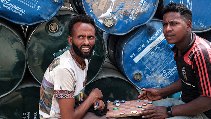 Men playing a board game by oil drums in Mekelle, Ethiopia - Friday 25 June 2021