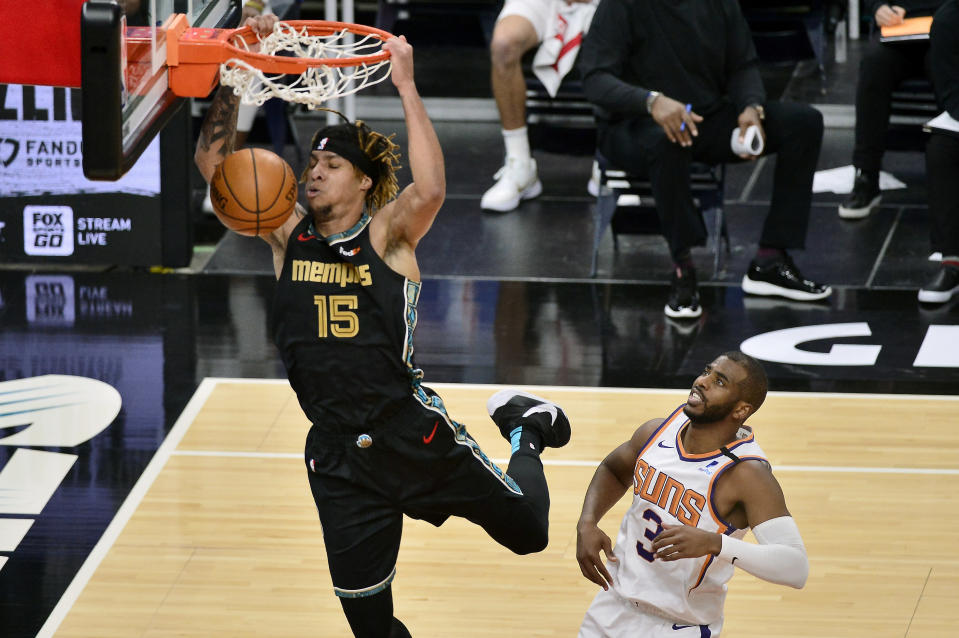 Memphis Grizzlies forward Brandon Clarke (15) dunks ahead of Phoenix Suns guard Chris Paul (3) in the first half of an NBA basketball game Monday, Jan. 18, 2021, in Memphis, Tenn. (AP Photo/Brandon Dill)
