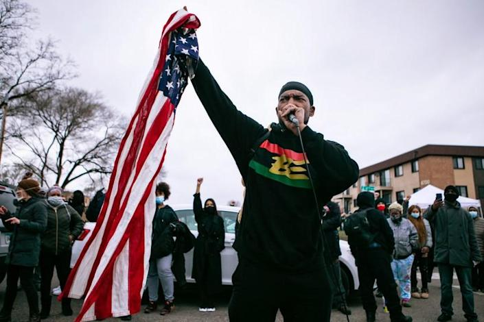 BROOKLYN CENTER, MN - APRIL 14: Michael Wilson, a community activist, speaks to the crowd of protesters gathered outside the Brooklyn Center Police Department calling for justice for Daunte Wright before curfew on Wednesday, April 14, 2021 in Brooklyn Center, MN. (Jason Armond / Los Angeles Times)