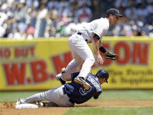 New York Yankees shortstop Jayson Nix, top, leaps over a sliding Tampa Bay Rays' Evan Longoria who was forced out after James Loney hit into a first-inning double play in a baseball game on Sunday, June 23, 2013, in New York. (AP Photo/Kathy Willens)