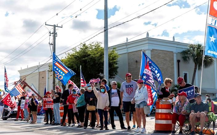 Supporters of Donald Trump gather along the route of his motorcade on Southern Boulevard as he arrives in Florida - AFP